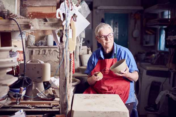 A woman in a blue shirt and red apron sits in a pottery studio holding an unglazed bowl
