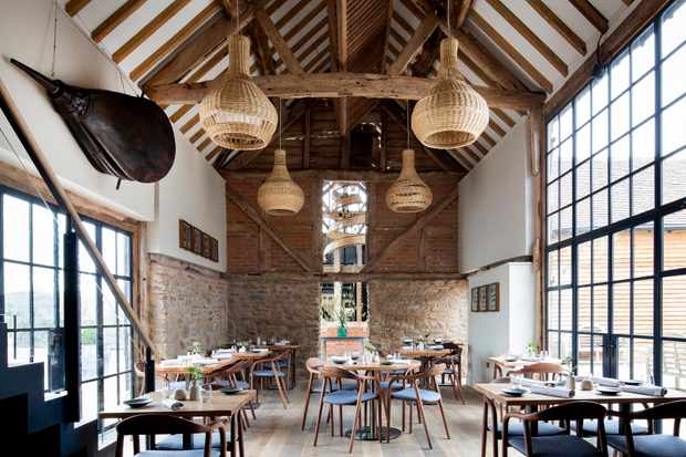 A old barn has been turned into a restaurant with exposed wooden beams and floor to ceiling windows