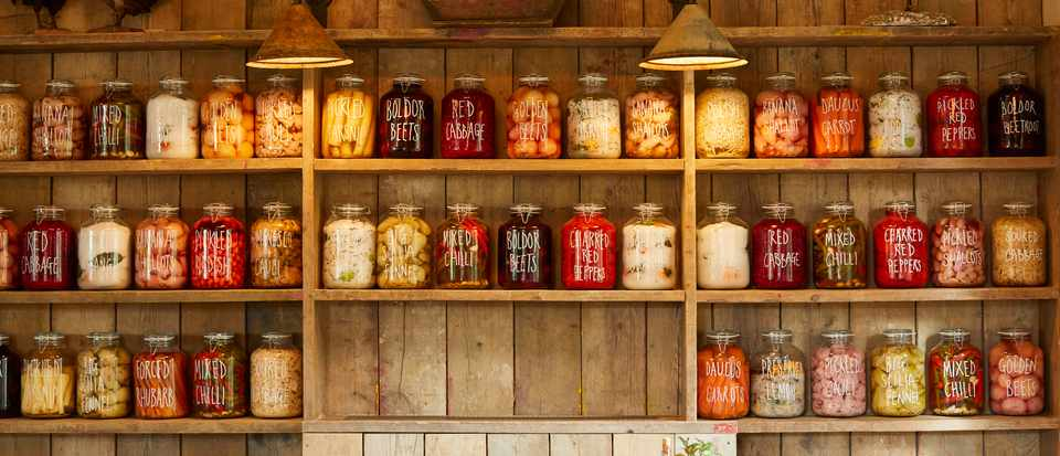 Wooden shelves lined with jars of pickles