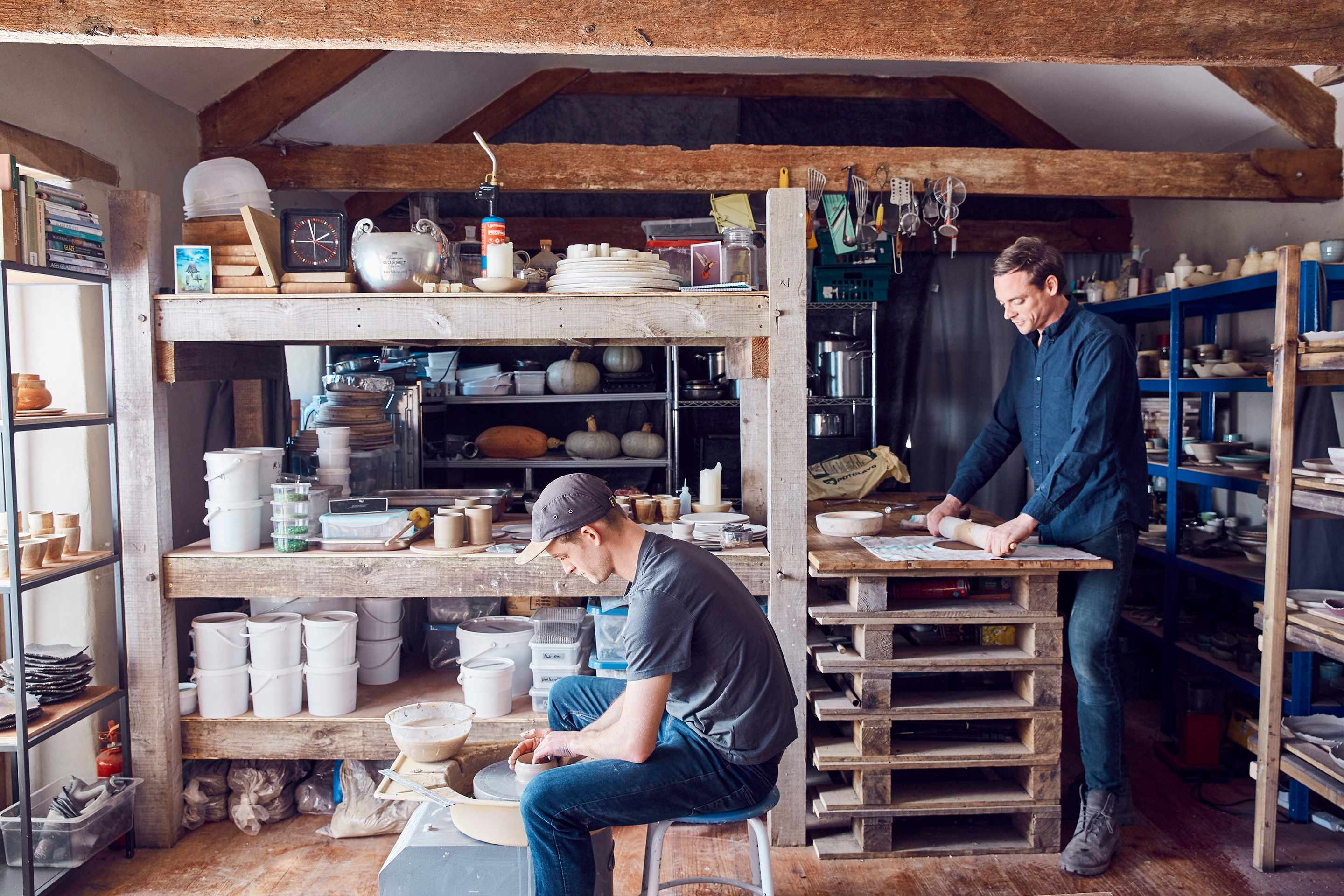 Two men are in a pottery studio. One is working around a wheel and the other is rolling out clay with a rolling stick