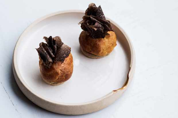 A white plate with beige rim has two savoury profiteroles in it