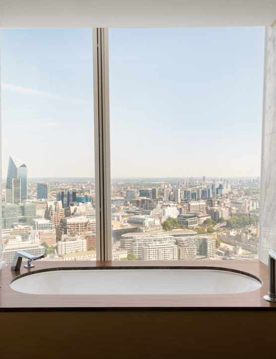 A bathtub in a hotel room which has a glass window looking out over London