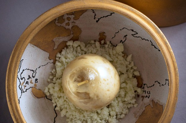 A gold ornate bowl with a map painted inside filled with a dessert made to look like an apple
