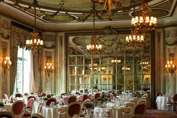 An opulent restaurant with mirrored walls, chandeliers and tables laid with white table cloths