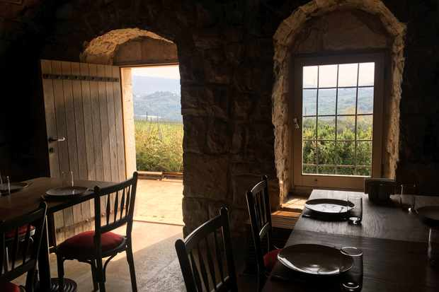 A stone building with tables and chairs has an open door that looks out over vineyards