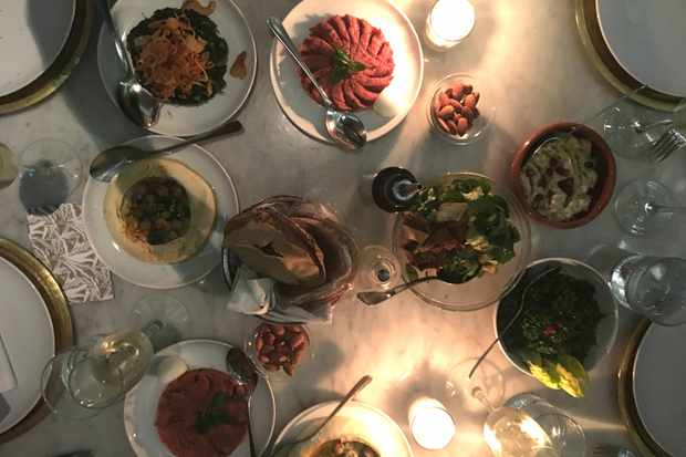 A candle-lit table has lots of small plates on it including flatbread and salad