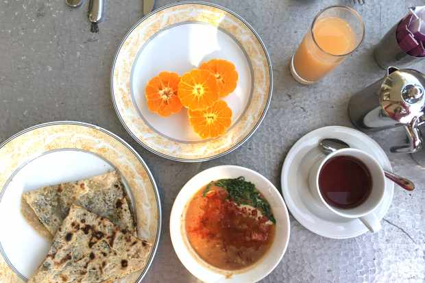 A table has a plate with orange slices on it, a coffee, a glass of juice and a plate with flatbreads on