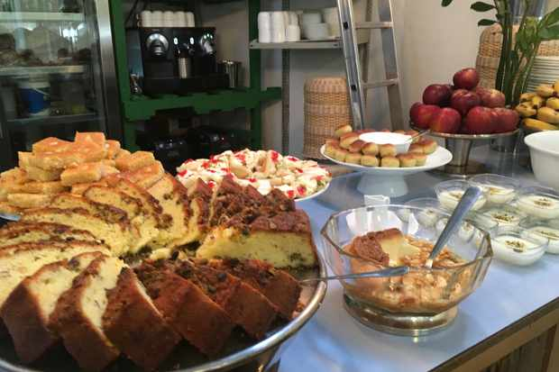 A counter is laden with cakes and desserts. There are slices of cake