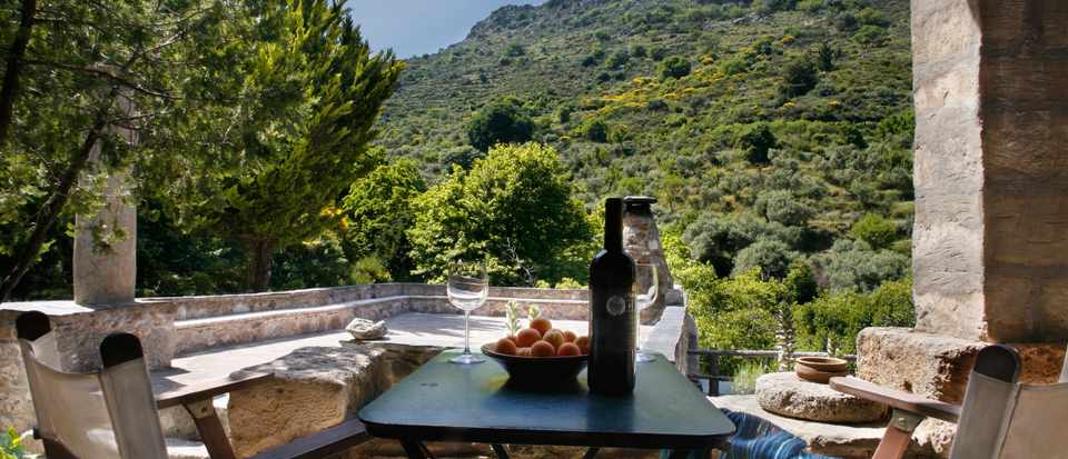 A table is laid with wine and it is looking out over rolling Greek hills