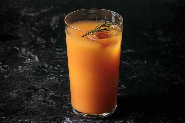 A long tumbler glass is filled with orange liquid and has green herbs on top