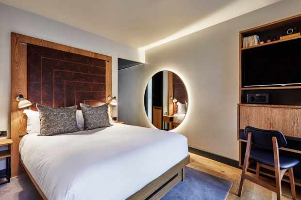 A minimalist bedroom with double bed, large circular mirror and wooden headboard