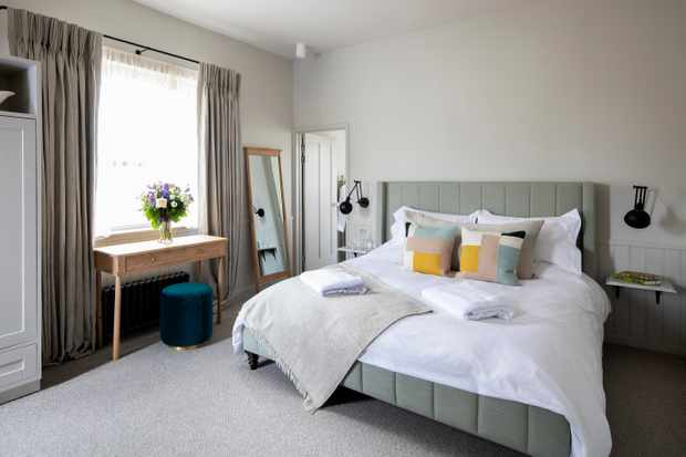 A large double bedroom with grey walls, a bed with white linen, a freestanding mirror and large sash window with dressing table underneath