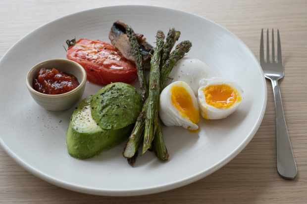 A white plate topped with asparagus, avocado, a boiled egg and tomato