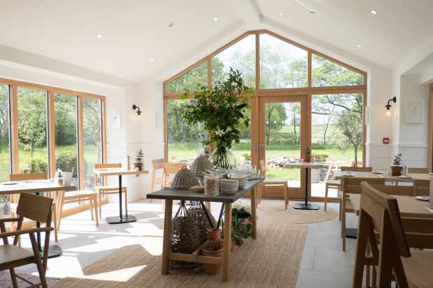 A light and airy room with floor to ceiling glass windows, wooden tables and chairs