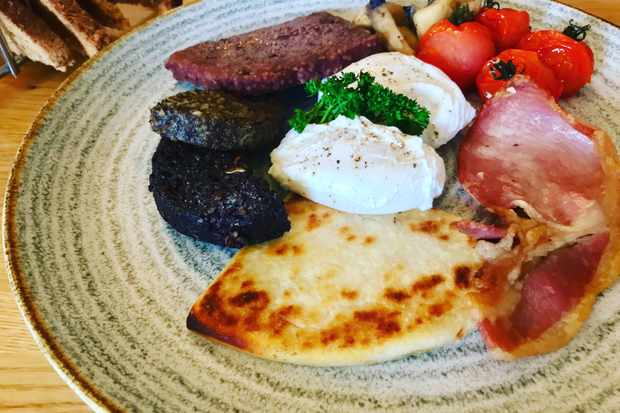 A plate is topped with two poached eggs, a rasher of bacon, roast tomatoes and a triangular potato cake