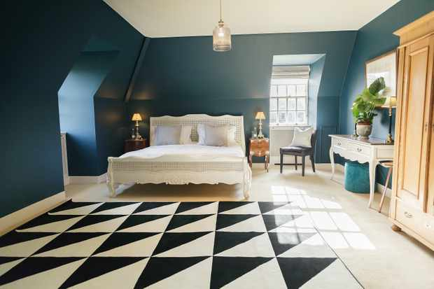 A large bedroom with double bed. There is a black and white chequerboard-style floor and teal-blue painted walls