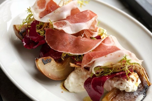 A white oval-shaped plate is topped with charred pears, burrata cheese and slices of pink ham