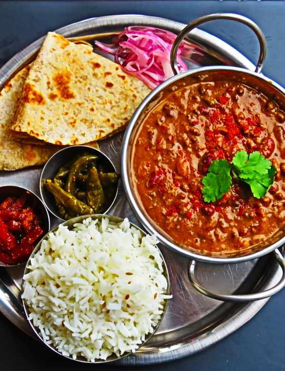 A platter of Indian food including rice, chapattis, daal and pickled onions