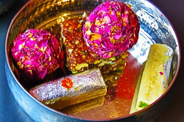 A silver tray filled with Indian sweet including halva