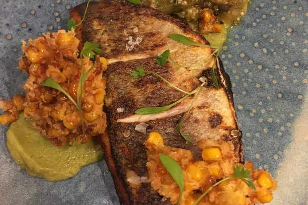 Pan-fried sea bass fillet with sweetcorn fritters, avocado purée and green tomato salsa