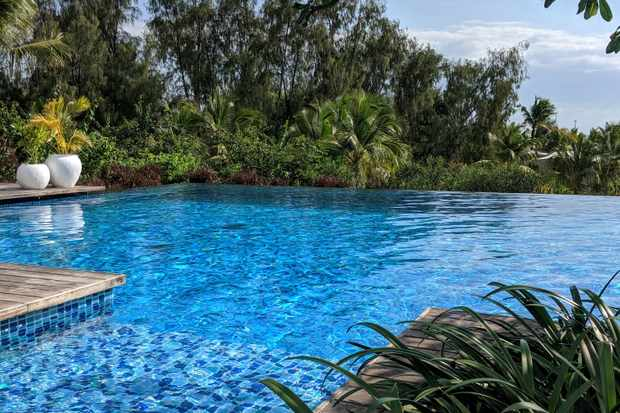 A bright blue infinity pool is surrounded by lush greenery
