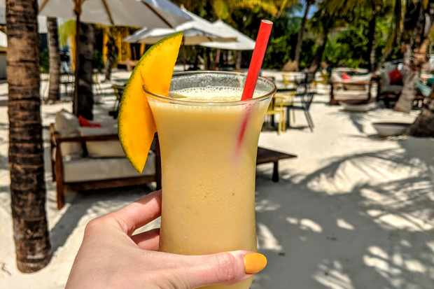 A woman is holding a long glass with yellow smoothie inside. There is a slice of mango on the side of the glass