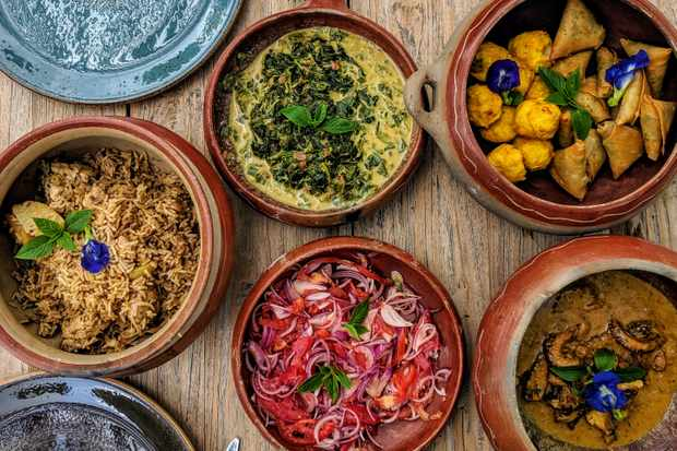 A wooden table is topped with many dishes, each filled with colourful food including octopus stew, samosas, tomato salad and chicken rice