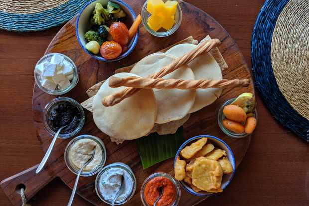 A large wooden board is topped with pitta breads, breadsticks and small pots each filled with different foods, from olive tapenade to pickled vegetables