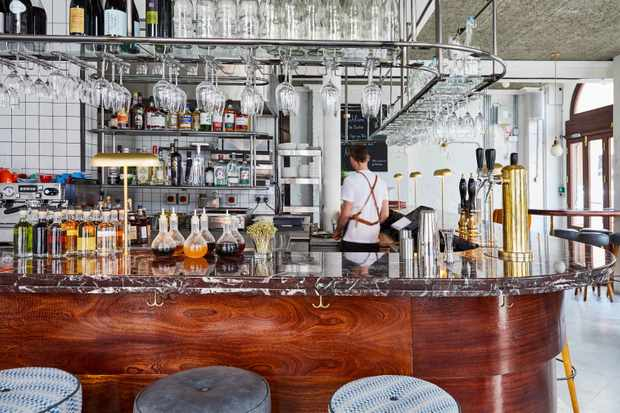 A striking bar with marble counter top. There is a man wearing an apron behind the bar and glasses lined up on top