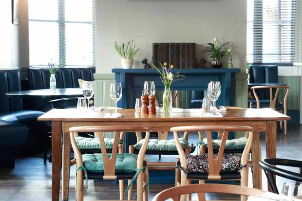 A dining room has a wooden table at the centre. There are pops of blue in the fireplace and furnishings