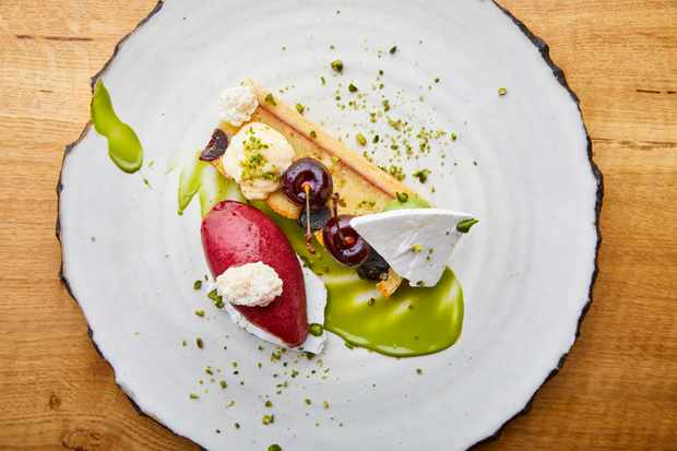 A circular plate is topped with a green sauce, a vibrant pink quenelle of sorbet, a tart and whole cherries