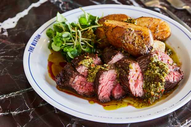 A white circular plate has slices of pink feather steak and a green sauce on top. There are chunky new potatoes to the side of the plate