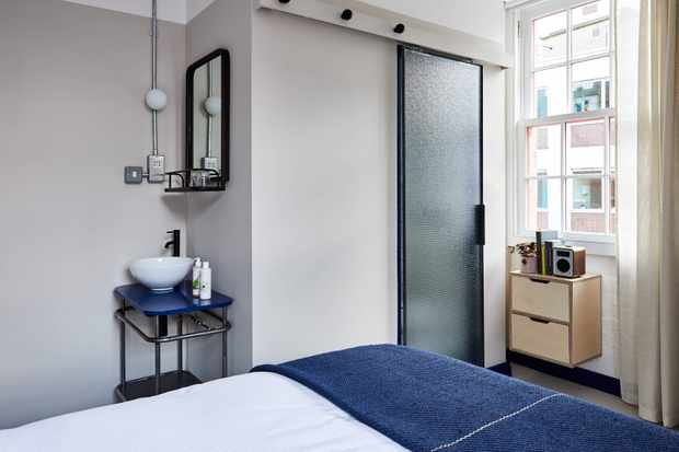 A small bedroom with the corner of a bed peaking in. The bed has white linen and a blue blanket, and there is a sink with a mirror in one corner of the room