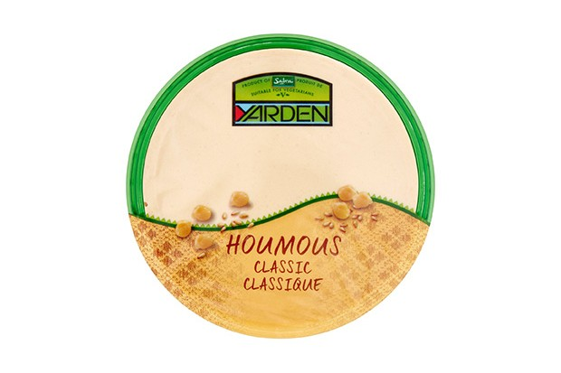 A cream pot with a green rim filled with hummus. The label says Yarden houmous classic