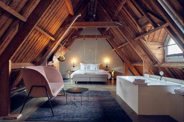 An attic room with exposed wooden beams, a large double bed and a rug on the floor with a pale pink sofa