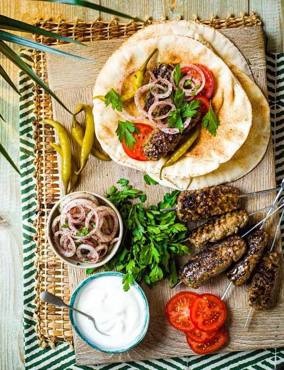 A wooden background has circular flatbreads with dark lamb skewers and a pot of white sauce and a pot of chopped onions