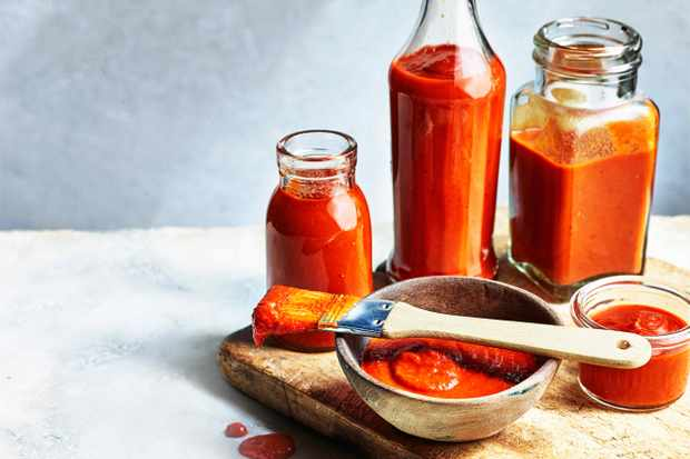 Three glass bottles and a small wooden dish all filled with a vibrant red sauce