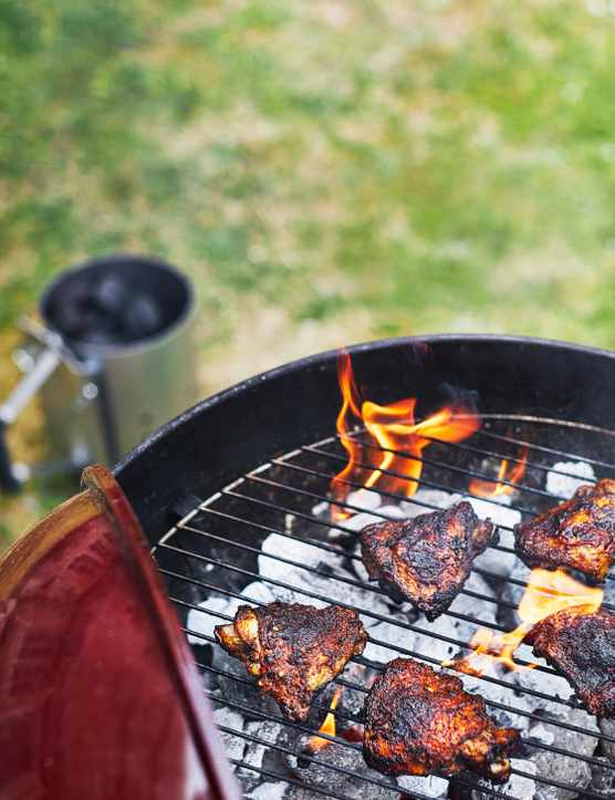 A BBQ with charcoal, a flame and chicken pieces on top