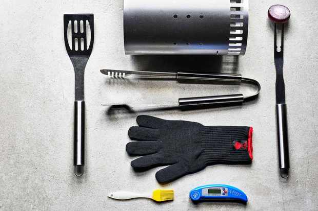 A grey background has a flatlay with bbq equipment on top. There is a glove, a digital probe, metal tongs and a skewer