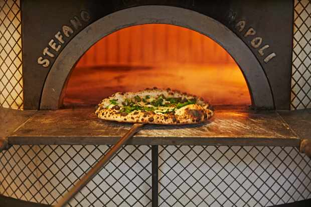 A large pizza oven with a pizza cooking inside