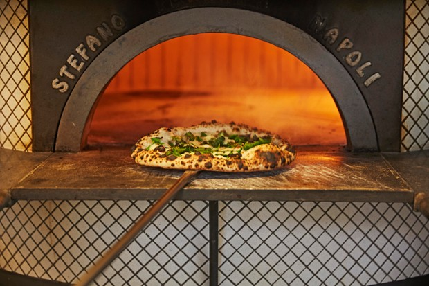 یک اجاق بزرگ پیتزا که داخل آن یک پیتزا پخته می شود