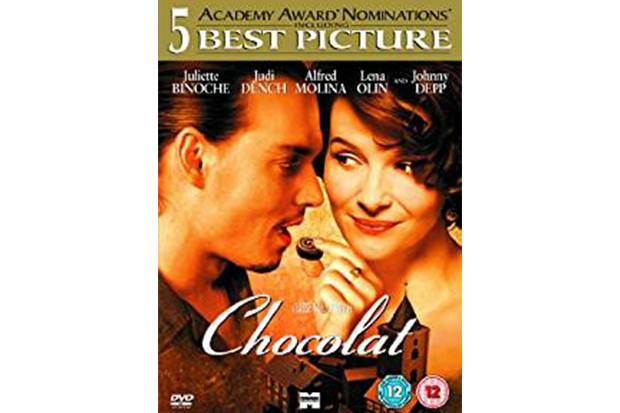 A DVD cover with a woman putting a chocolate towards a mans lips