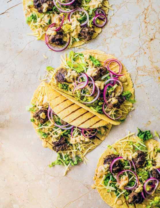 Yellow tortilla wraps filled with mince, red onion and salad leaves