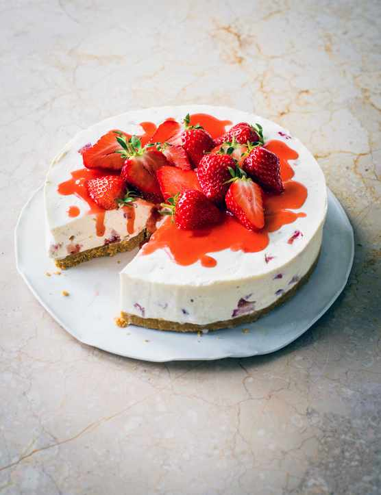 A white cheesecake topped with red strawberries and whole strawberries on a white plate