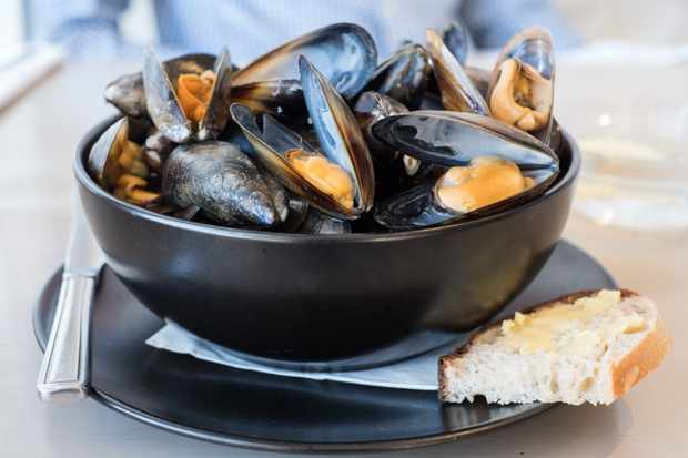 A black bowl filled with open mussels