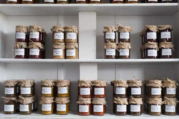 A white wall lined with jars of jam