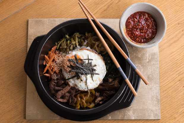 A black bowl filled with rice, vegetables and beef with chopsticks balanced on top