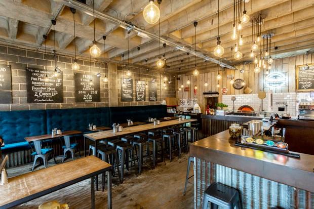 یک اتاق ناهار خوری بزرگ با چهارپایه های مرتب ، میزهای چوبی بلند و تخته سیاه