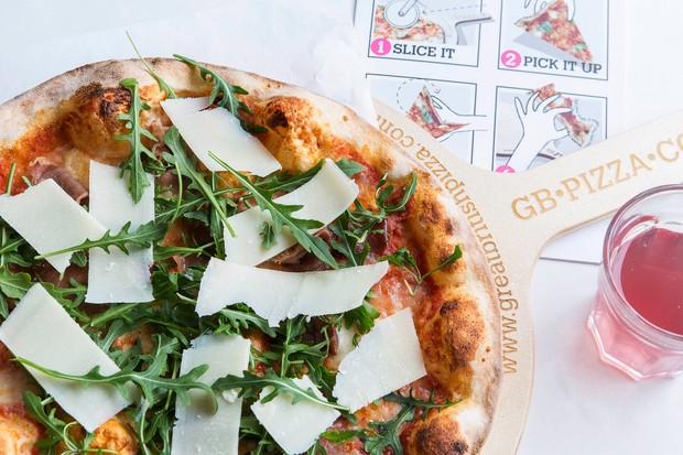 یک پیتزا که برگهای سبز و پنیر تراشیده شده روی آن است