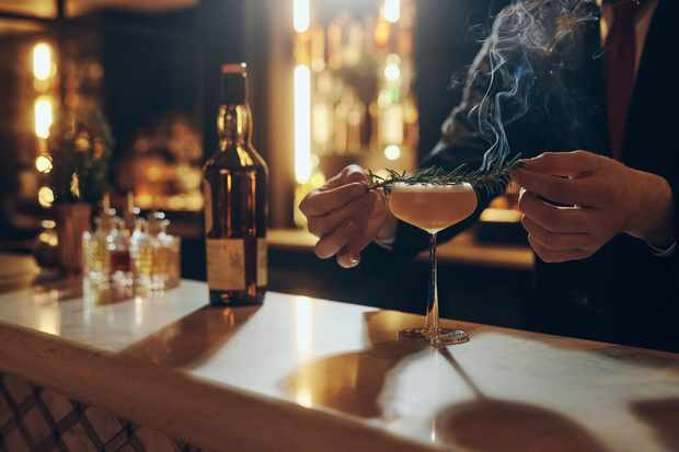 A dark photograph shows a person adding a garnish to a cocktail